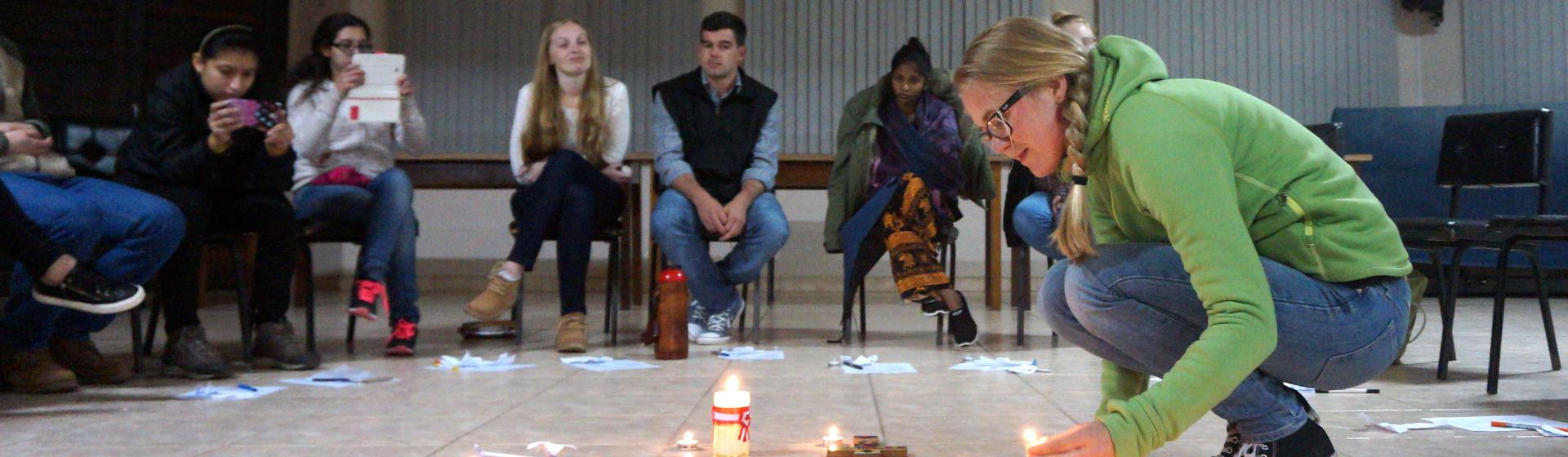 A participant at the international youth gathering in Brazil lights a candle