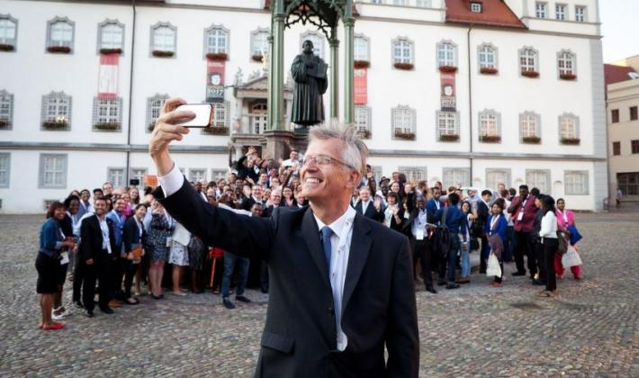 LWF General Secretary Rev Dr Martin Junge posing with young reformers and a statue of Martin Luther in Wittenberg, Germany
